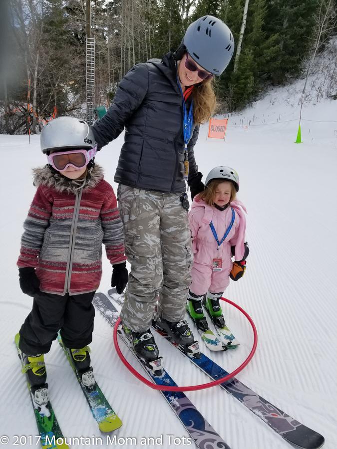 Mom and two girls skiing with hula hoop