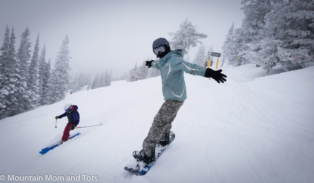 Snowboarding woman on a powder day at Grand Targhee Resort Wyoming